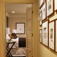 In this traditional San Francisco hallway, the owner mixes different sizes of the same wood custom frame, but maintains order by aligning the lowest row of frames.  Get started today and find a perfect modern frame at framed & matted.